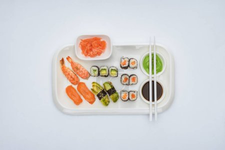 top view of delicious sushi set with chopsticks isolated on white