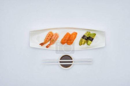 Photo for Top view of gourmet sushi, soy sauce and chopsticks isolated on white - Royalty Free Image