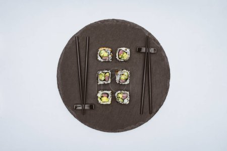 top view of delicious sushi and chopsticks on round slate board isolated on white