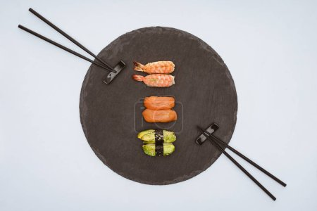 top view of delicious sushi on slate board and chopsticks isolated on white