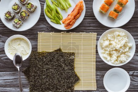 top view of nori sheets and ingredients for preparing delicious sushi on wooden table