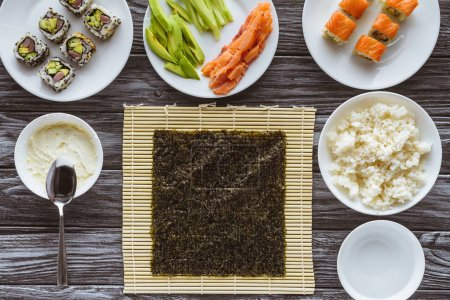 top view of nori and delicious ingredients for cooking sushi on wooden table
