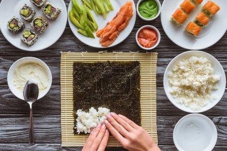 Photo pour Vue de dessus partielle de la personne qui prépare les sushis avec du riz, nori et ingrédients - image libre de droit