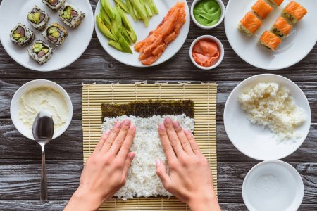 partial top view of person preparing sushi with rice and nori, gourmet ingredients on table