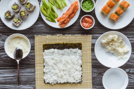 Photo for Top view of rice, nori and ingredients for sushi on wooden table - Royalty Free Image