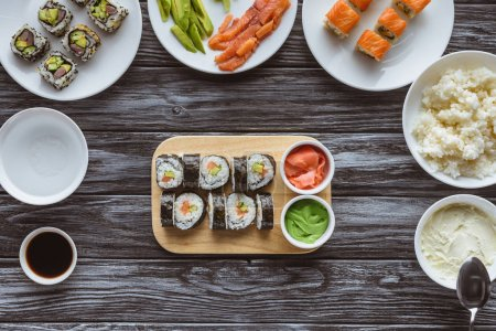 top view of delicious sushi rolls with ingredients on wooden table