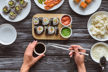 cropped shot of person holding chopsticks and eating delicious sushi