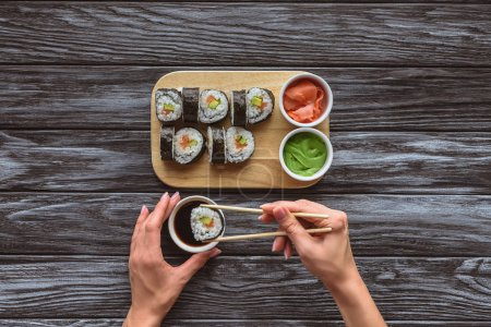 partial top view of person holding chopsticks and eating delicious sushi roll
