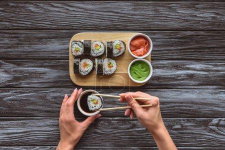 vue de dessus partielle de la personne tenant les baguettes et manger de délicieux sushi roll
