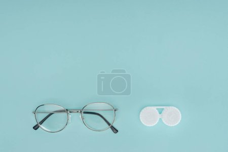 top view of eyeglasses and contact lenses container on blue background