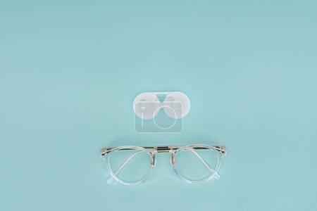 Photo pour Vue de dessus des lunettes et lentilles de contact conteneur sur fond bleu - image libre de droit
