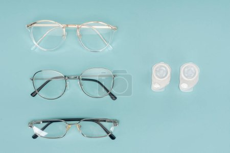 top view of eyeglasses and contact lenses containers arranged on blue background