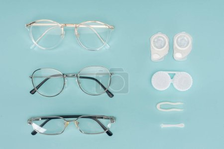 top view of eyeglasses, contact lenses containers and tweezers arranged on blue background