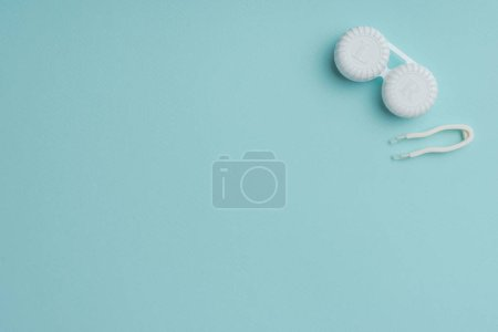 top view of white contact lenses container and tweezers on blue background