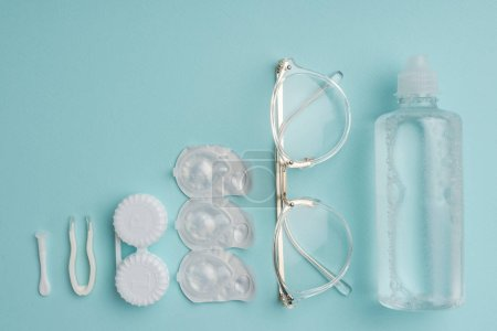 top view of eyeglasses and contact lenses storage objects arranged on blue background