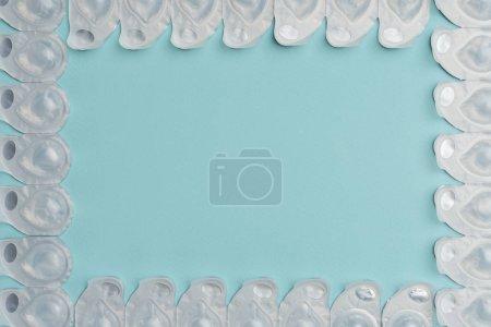 Photo pour Pose plate avec lentilles de contact dans des récipients disposés sur fond bleu - image libre de droit