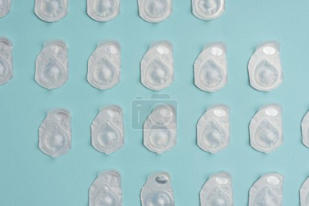 full frame of contact lenses in containers arranged on blue background