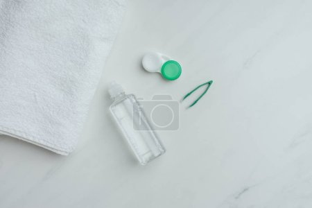 Photo for Flat lay with towel and contact lenses storage equipment arranged on white tabletop - Royalty Free Image