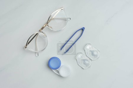 Photo for Flat lay with eyeglasses, contact lenses containers and tweezers arranged on white surface - Royalty Free Image