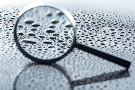 Photo for Close up view of magnifying glass and water drops on grey backdrop - Royalty Free Image