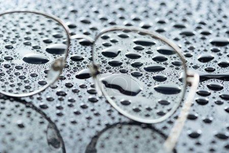 Photo pour Vue rapprochée des lunettes et des gouttes d'eau sur fond gris - image libre de droit