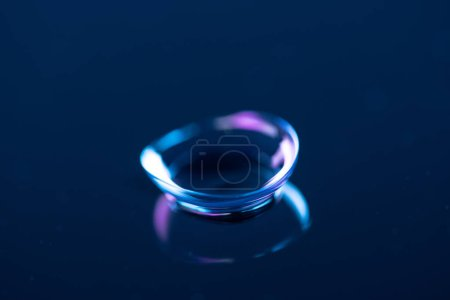 close up view of contact lense on blue backdrop