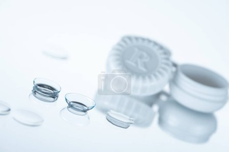 selective focus of contact lenses and container on white backdrop