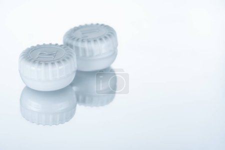 close up view of contact lenses container on background with reflection
