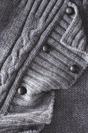close up view of grey knitted cloth with buttons as backdrop