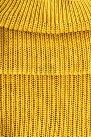 close up view of folded bright yellow woolen fabric as backdrop