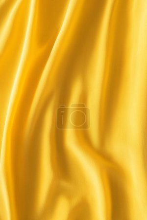 full frame of wavy yellow silk cloth as background