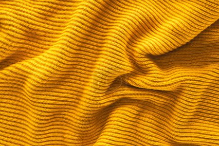 close up view of wavy yellow woolen fabric backdrop