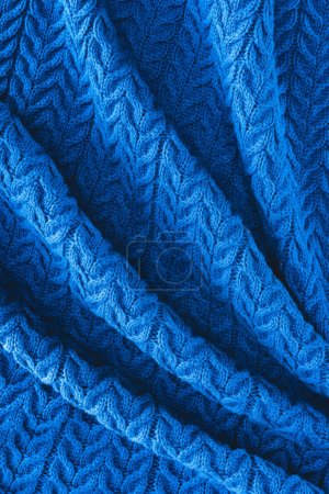 full frame of folded dark blue woolen fabric with pattern as backdrop