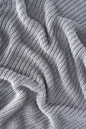 full frame of wavy grey knitted cloth as backdrop