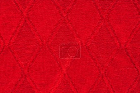 close up view of red woolen fabric with pattern as backdrop