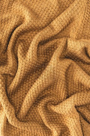 full frame of folded brown textured fabric as backdrop
