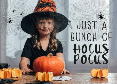"portrait of adorable kid in witch halloween costume sitting at table with pumpkin at home with ""just bunch of hocus pocus"" lettering"