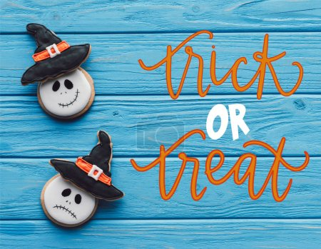 """elevated view of delicious homemade halloween cookies on wooden background  with """"trick or treat"""" lettering"""