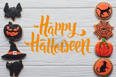 "elevated view of arranged homemade halloween cookies placed in rows on white wooden background  with ""happy halloween"" lettering"