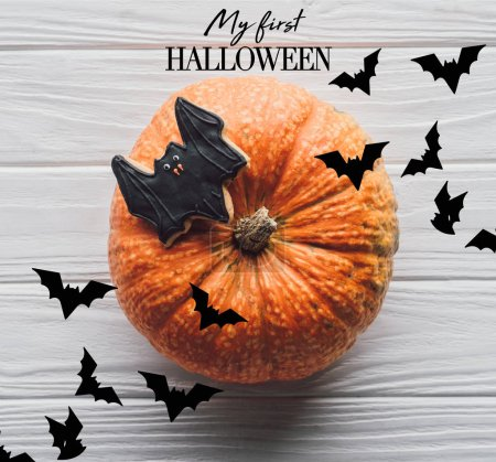 """elevated view of pumpkin with homemade halloween cookie on wooden table with """"my first halloween"""" lettering"""