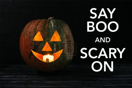 """jack o lantern pumpkin with candle inside on wooden table on black background with """"say boo and scary on"""" halloween lettering"""