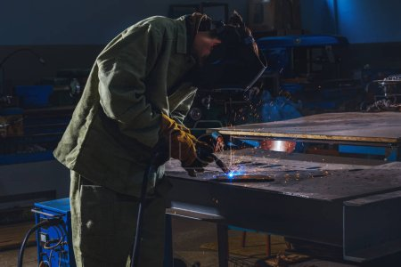 Concentrated manufacture worker welding metal with...
