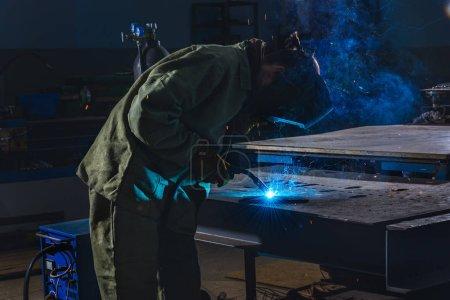 Photo pour Vue de côté de soudeur dans le masque de protection métallique à l'usine de soudure - image libre de droit
