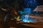 partial view of welder in protection mask brazing metal at factory