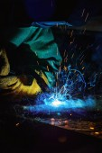 focused welder in protection mask brazing metal at factory