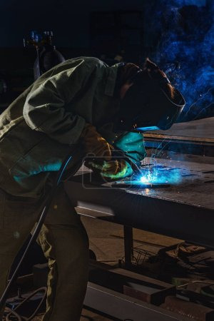 male manufacture worker welding metal with sparks at factory