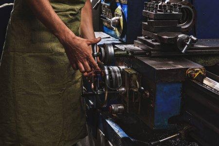 Photo pour Cropped image de fabrication mâle ouvrier en tablier de protection à l'aide de machines-outils à l'usine - image libre de droit