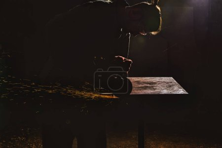 side view of manufacture worker in protective googles working with circular saw at factory