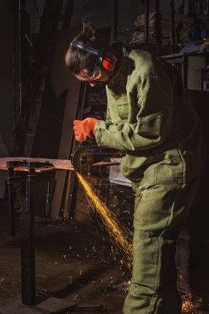 manufacture worker in protective googles working with circular saw at factory