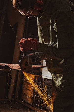 focused male worker in protective googles working with circular saw at factory